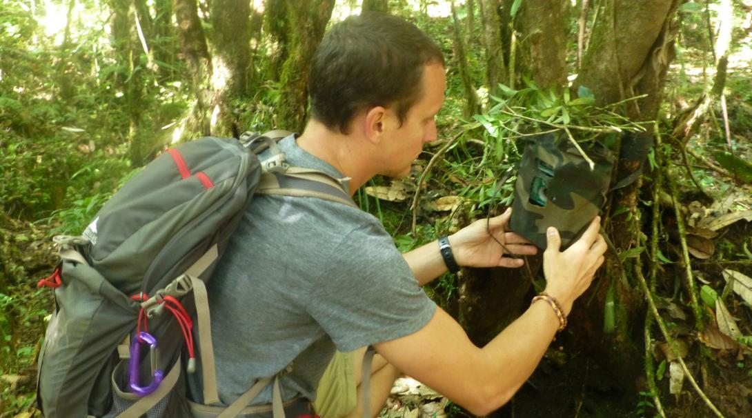 Projects Abroad naturskyddsvolontär sätter upp en kamerafälla i en nationalpark i Himalaya